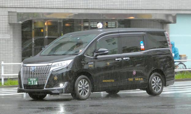 激しく降る雨の中を走るタクシー