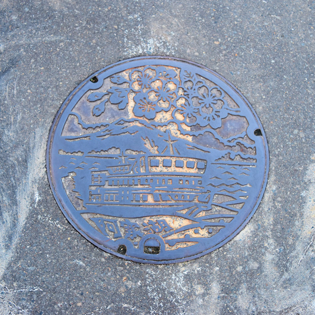 阿寒町のマンホール(阿寒湖と観光船と桜の図柄・モノクロ版)