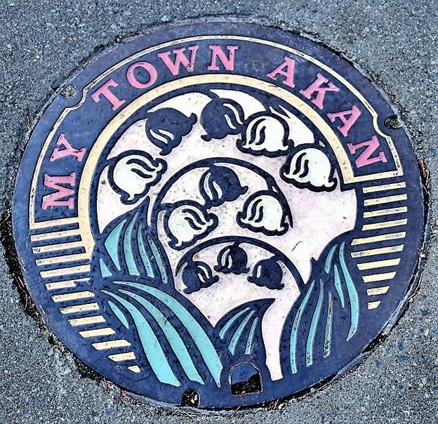 085-0215釧路市(旧阿寒町)のマンホール(スズランの図柄とマイタウンの文字・カラー版)