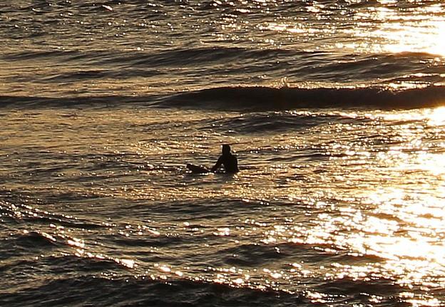夕陽輝く海で波を待つ